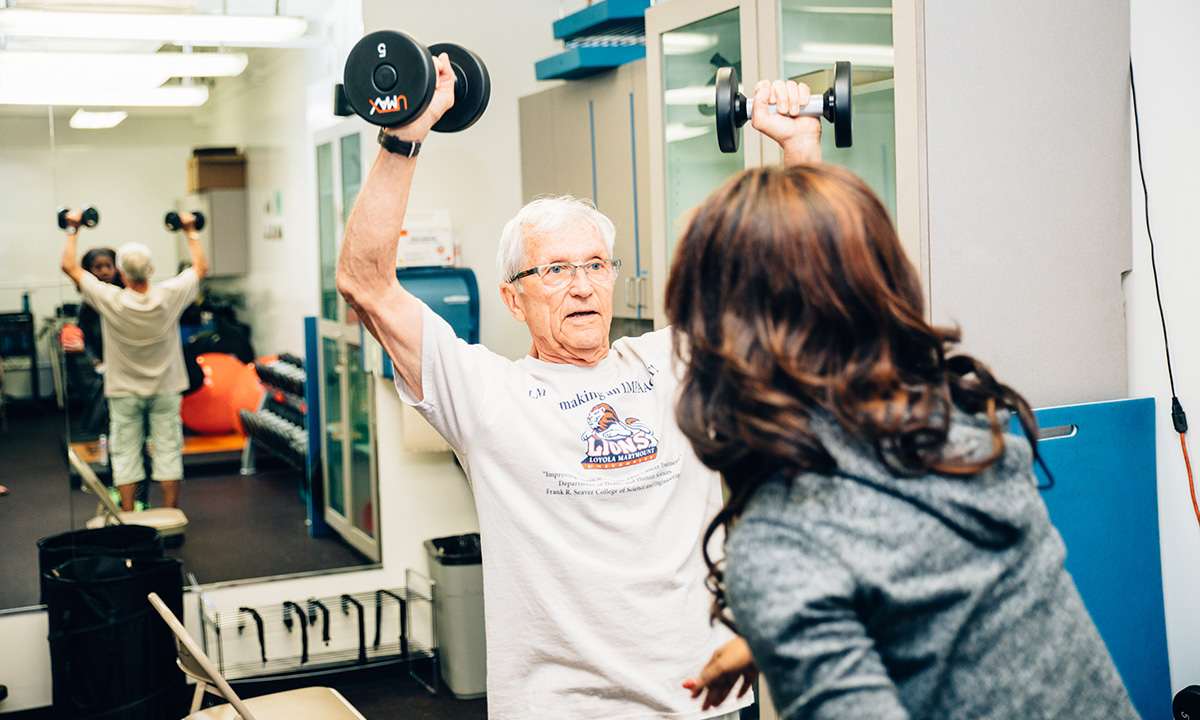 A personal trainer working with a senior staff member who is learning to properly lift weights
